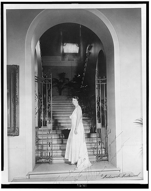 [Eleanor Roosevelt, full-length portrait, standing at bottom of the Grand Staircase in the White House, facing left]