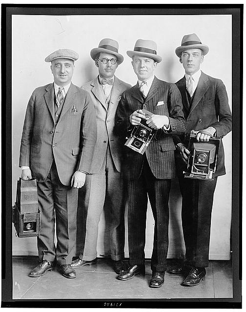 [Group portrait of four members of the White House News Photographers&#39; Association, standing, facing front, holding cameras]