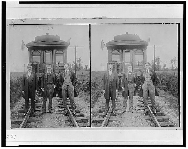 [Theodore Roosevelt, full-length portrait, standing, with two other men in front of railroad observation car]