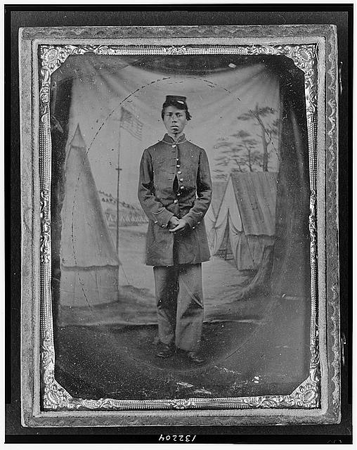 [Standing soldier, frock coat, kepi, painted background, dirt floor, done by traveling camp photographer]