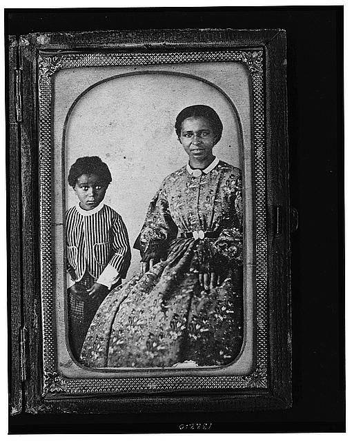 [Full-length portrait of an unidentified woman, seated, and full-length portrait of a child standing on her right, both subjects are facing front]