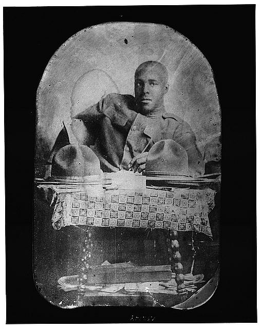 [World War I soldier, half-length portrait, seated, facing front, with two hats on table]