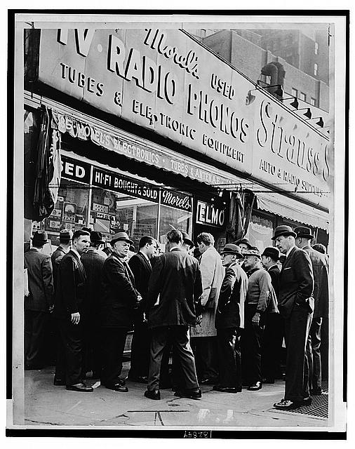 Crowd listens outside radio shop at Greenwich and Dey Sts. for news on President Kennedy