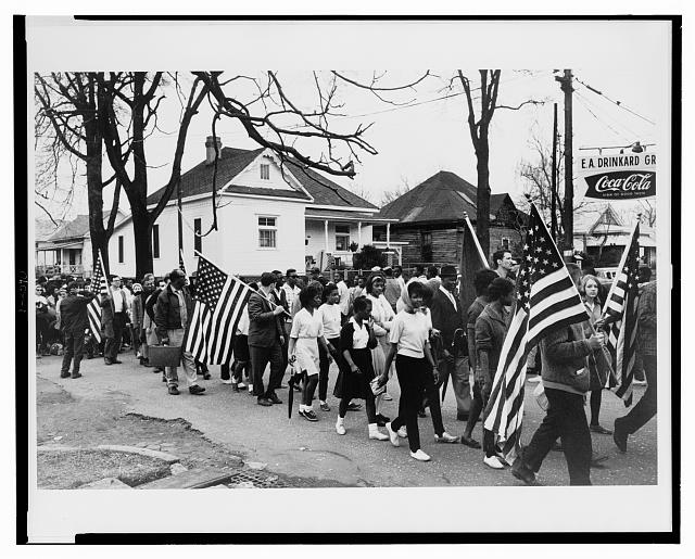 [Participants, some carrying American flags, marching in the civil rights march from Selma to Montgomery, Alabama in 1965]