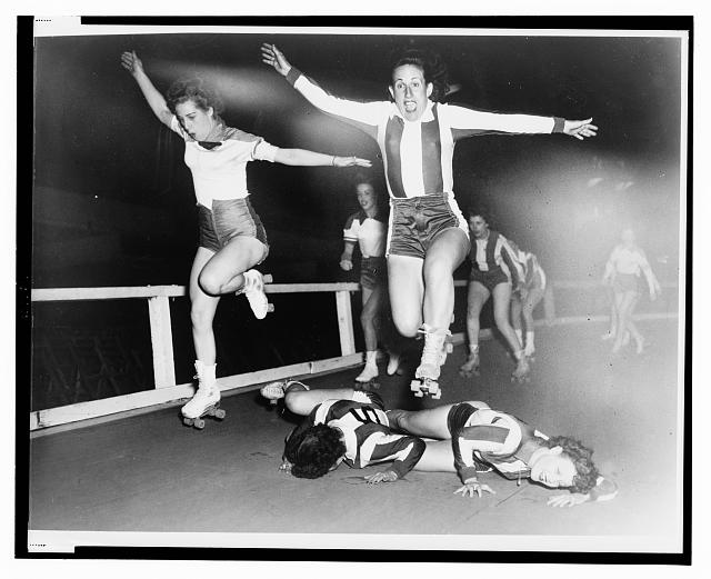 [Two women's league roller derby skaters leap over two who have fallen]