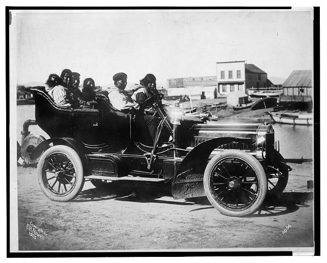 [Eskimos, five adults and one infant, sitting in an automobile]