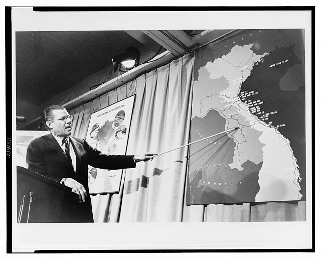 Sec. of Defense Robert McNamera pointing to a map of Vietnam