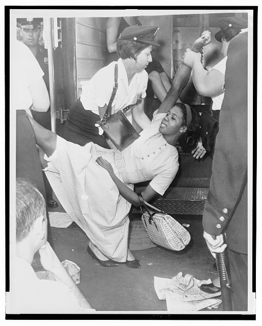 [African American woman being carried to police patrol wagon during demonstration in Brooklyn, New York]