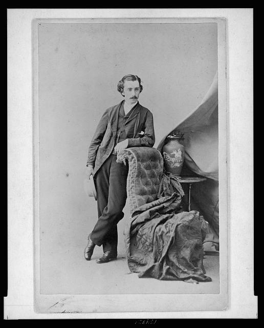 [John Bishop Putnam, full-length studio portrait, facing slightly right, leaning on chair]