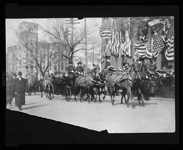 [Theodore Roosevelt sitting in an open carriage enroute to the U.S. Capitol on his inauguration day tips his hat to spectators]
