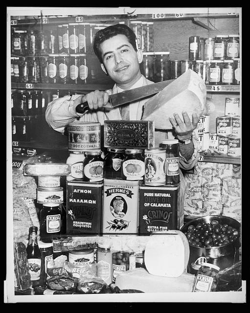 Gus Marris is shown with a large display of Greek foods at the Couphopoulos Delicatessen at 306 W. 40th St.