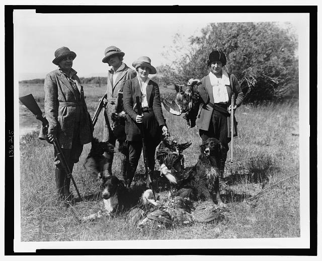 [Five women hunters posed with their dogs and dead birds]