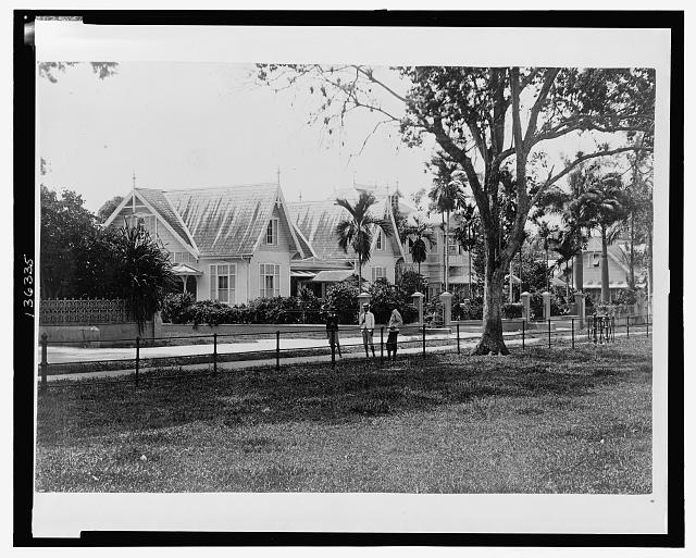 [Three British(?) boys standing on a sidewalk in a residential neighborhood, Port of Spain, Trinidad and Tobago]