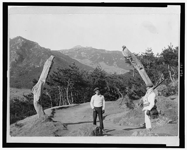 Korea. Posts along road which were carved to prevent devils from passing