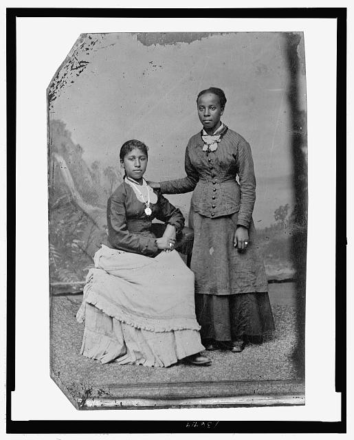 [Portrait of two young African American women, one standing, one seated]
