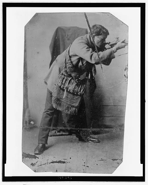 [Full-length portrait of a man with a fringed, knitted bag across his chest, posed as if shooting a rifle]