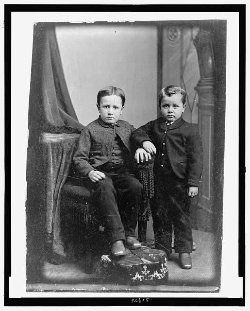 [Two boys, one seated, one standing]