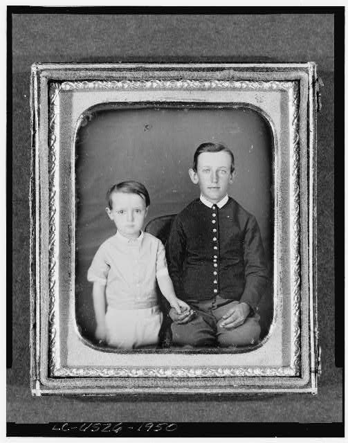 [Unidentified boy seated in chair with child standing to left, three-quarter length, facing front]