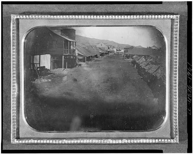 [View of an unidentified village with ship in background]