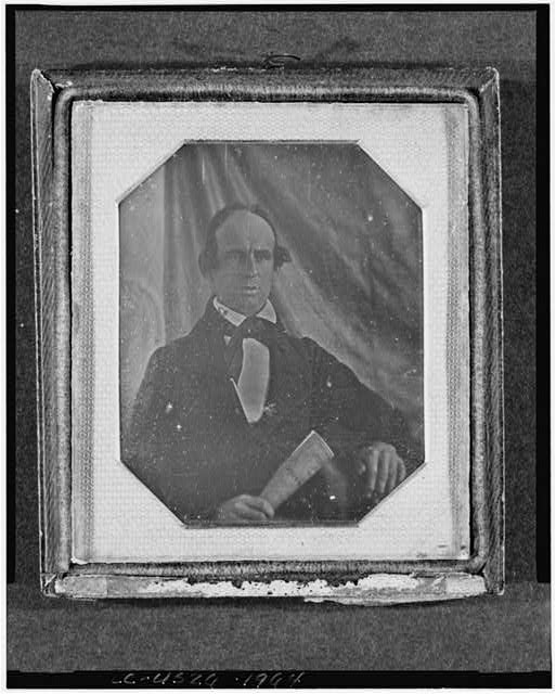 [Unidentified man, head-and-shoulders portrait, full face, seated, holding a printed sheet]