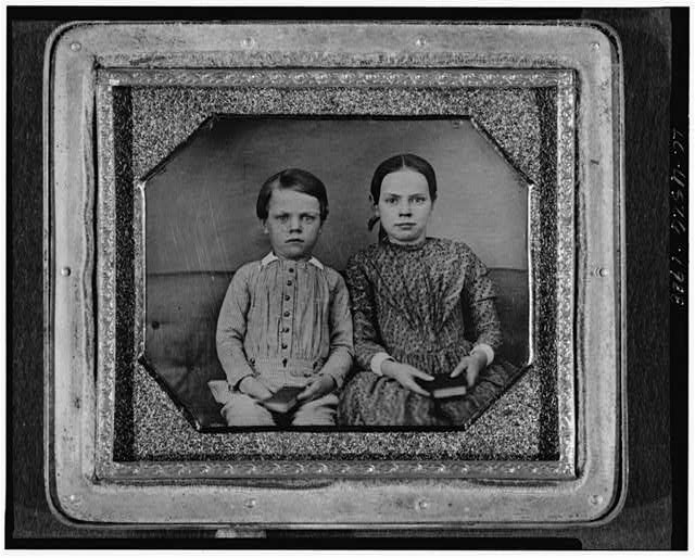 [Group portrait of an unidentified boy and girl, three-quarter length, seated on upholstered bench, facing front, holding books]