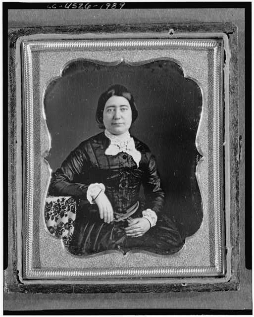 [Unidentified woman, three-quarter length portrait, facing front, seated with arm resting on table with tablecloth]