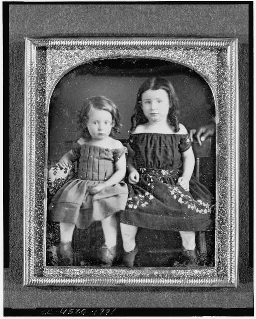 [Two unidentified girls, full-length portraits, seated on chairs next to table with tablecloth]