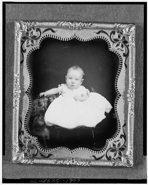 [Harrison Grey Fiske, full-length portrait of six month old baby boy, seated on chair, propped next to table with tablecloth]