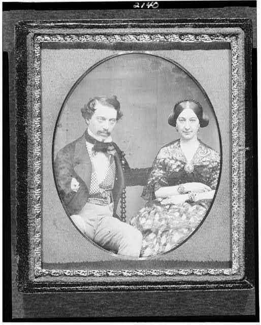 [Hickson W. and Mary Elizabeth Field, three-quarter length portrait of a man seated in a chair beside a woman with elaborate jewelry]