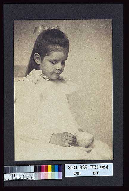 [Young girl in white dress, seated holding teacup and saucer]
