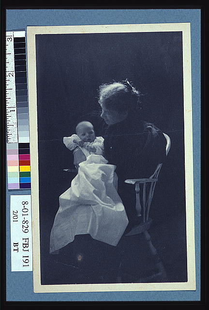 [Woman, sitting in chair, holding an infant, full-length portrait]