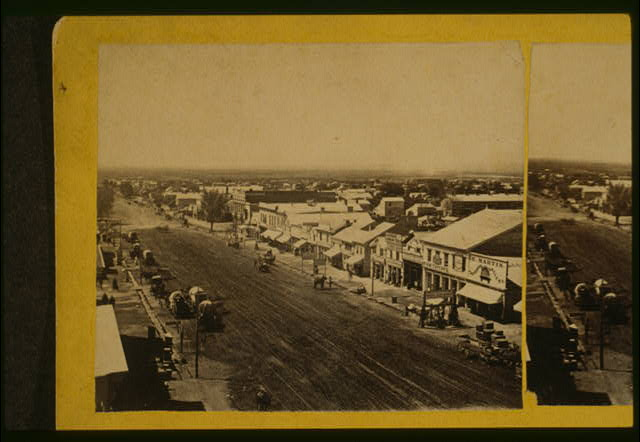 [Aerial view of commercial street in Salt Lake City, Utah, with horse drawn wagons, and in the background, urban sprawl]