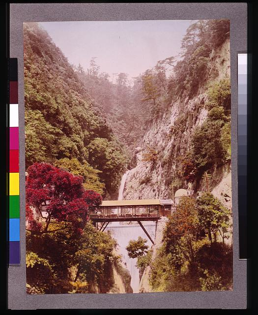 [Covered bridge in a steep gorge, with waterfalls in the background, in Japan]