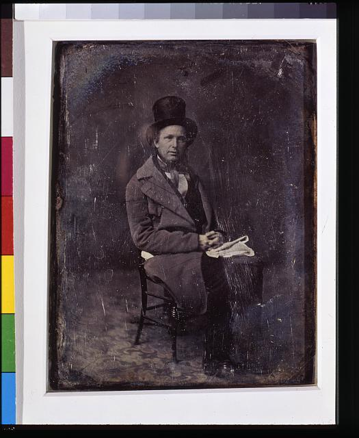 [Horace Greeley, full-length portrait, three-quarters to the right, seated in chair, wearing tall hat, folded newspaper in lap, carpet on floor]