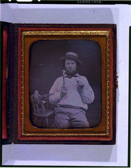 [Occupational portrait of a carpenter, three-quarter length, seated, facing front, holding hammer and nail, on a chair at his side are a saw, box plane, and measuring device]