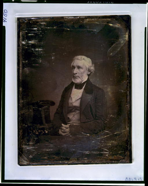 [James Gordon Bennett, three-quarter length portrait, three-quarters to the left, seated, hands folded in lap, seated beside a small table with tablecloth on which rests a tall hat]
