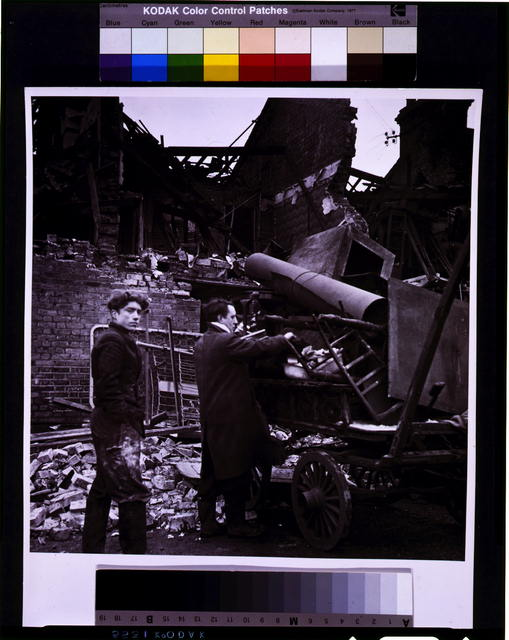 [Battersea incident, England, January 1945--two men load a wagon with their possessions, among ruins]