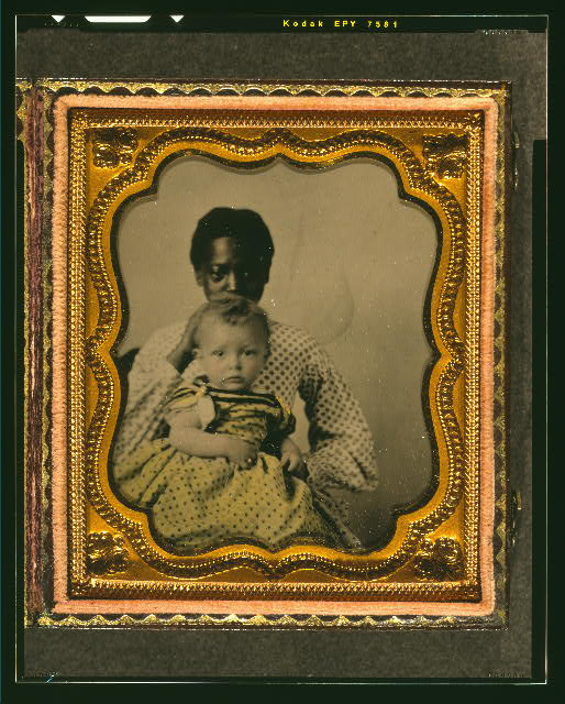 [African American woman holding a white child]