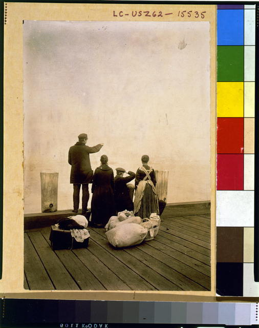 [Four immigrants and their belongings, on a dock, looking out over the water; view from behind]
