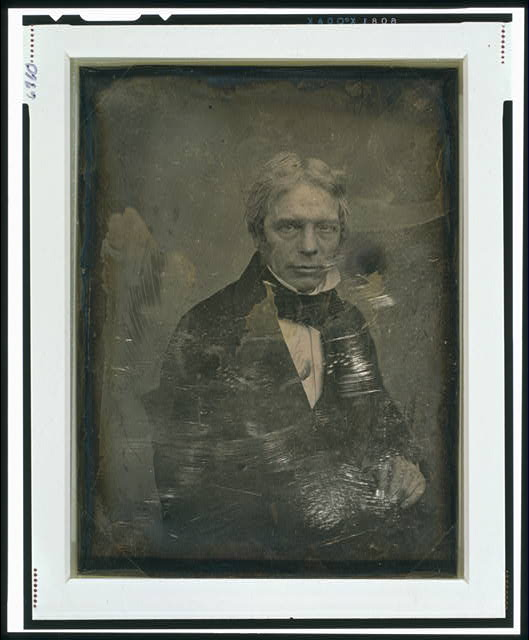 [Michael Faraday, half-length portrait, three-quarters to the right, seated in chair, hand resting on table]