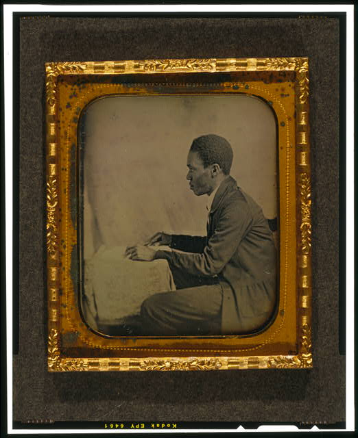 [C.H. Hicks, in profile, seated at desk]