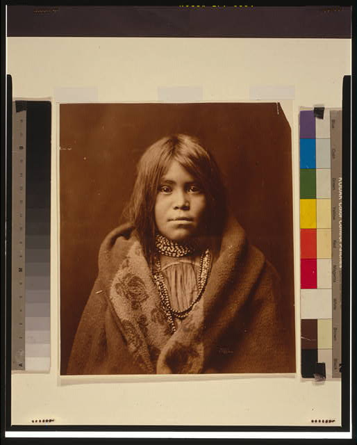 [An Apache girl, head-and-shoulders portrait, facing front, wearing bead necklace, with blanket around her]