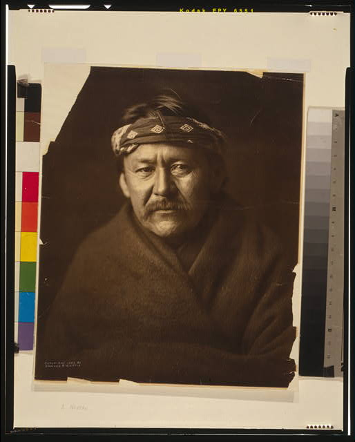 [A Navajo man, head-and-shoulders portrait, wearing blanket and headband, facing front]
