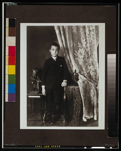 [African American boy, full-length portrait, standing,  facing front with left hand resting on table]