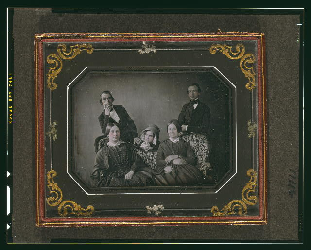 [Two unidentified women seated on a sofa, two unidentified men standing behind the sofa, with a woman peering over the back of the sofa]