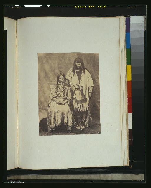 [Kalispel couple, full-length portrait, the man standing, the woman seated, facing front, wearing traditional dress]