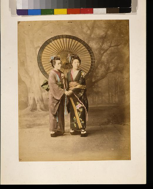 [Two Japanese women, full-length studio portrait with backdrop, facing slightly right, standing with large parasol and holding hands]