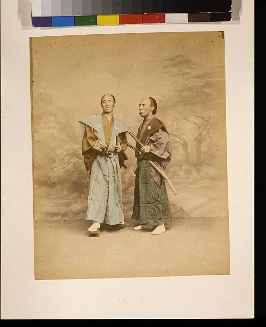 [Two Japanese men, possibly samurai, full-length studio portrait with backdrop, standing, one facing front and the other facing left, each with two swords]