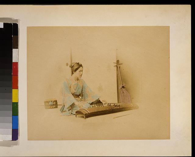[Japanese woman, full length, seated, facing right, playing a koto; a shamisen leans against a wall in the background]