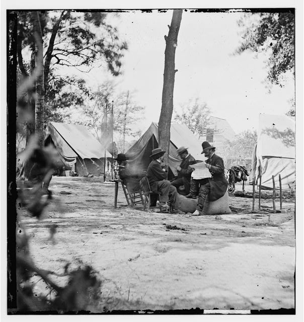 [Gen. Ambrose E. Burnside (reading newspaper) with Mathew B. Brady (nearest tree) at Army of the Potomac headquarters]